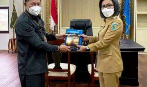 >> Kepala BPS saat menyerahkan buku data stasistik Bolmong, kepada Bupati Bolmong.