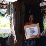 >> Penyerahan bantuan sembako oleh personil Sat Lantas Polres Bitung kepada warga kurang mampu.(ist)