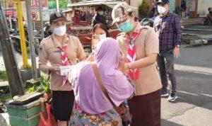 >> Ketua Kwarcab Pramuka Tomohon, drg Jeand'arc Karundeng saat berbagi masker ke pejalan kaki.