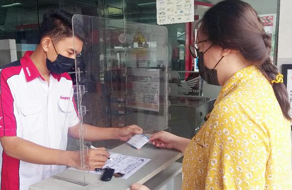 >> Konsumen menunjukan kartu vaksin kepada petugas AHASS saat melakukan servis Motor Honda.